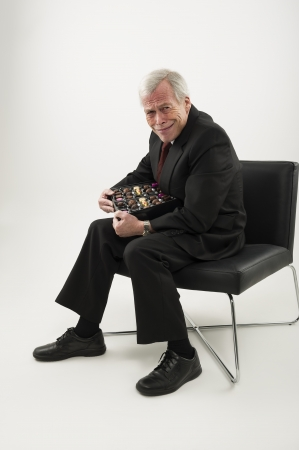 covetous: Studio portrait over white of an old man in a suit, sitting in a chair and protecting a large box of chocolates from anyone who may wish to share