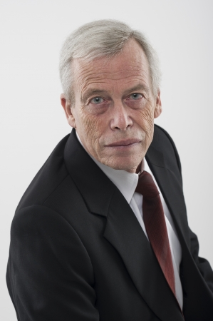 gray suit: High angle studio portrait of a serious handsome grey haired senior man in a suit and tie looking up at the camera
