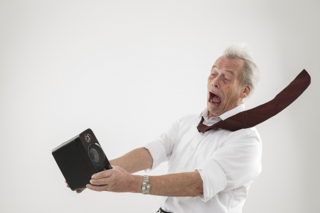 Conceptual studio shot over white of an old man being blasted by a sound wave from an audio speaker photo