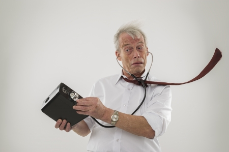 deafening: Conceptual studio shot over white of an old man with a hearing problem, who is using a stethoscope to try and hear his audio speakers