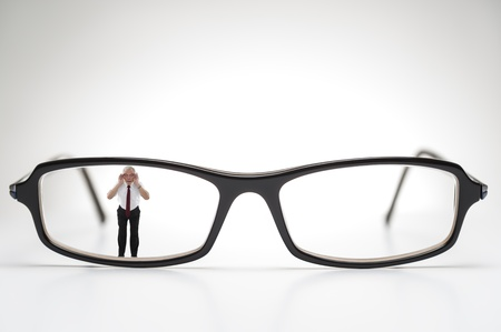 Diminutive elderly man peering through a lens on a pair of spectacles or prescription glasses , a humorous take on aging eyesight requiring corrective glasses