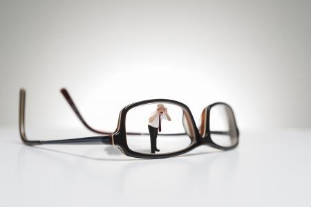 Conceptuele foto van levensgrote glazen en een mannelijk model die door een zijde van de bril.