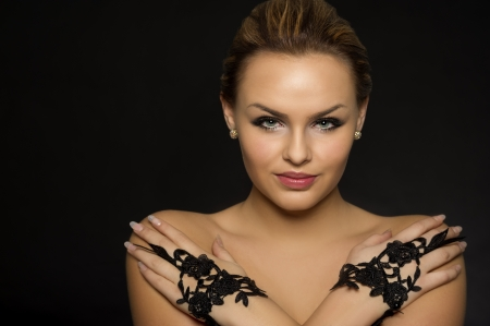 tantalising: Portrait of a glamorous woman wearing elegant black lace gloves