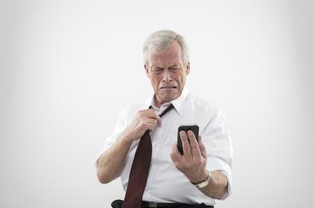 Knappe senior man los te maken zijn stropdas reageren in walging en afkeer om een inkomend gesprek of tekstbericht op zijn mobiele trok een gezicht en grimassen. Stockfoto