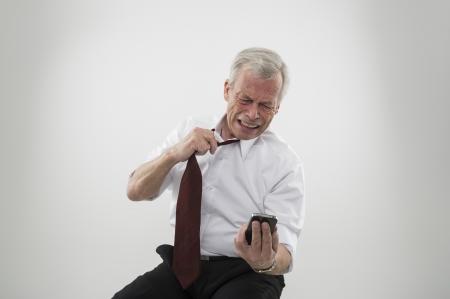 anguished: Angosciato anziano gey uomo dai capelli allentando la cravatta la lettura di un messaggio sullo schermo del suo telefono cellulare reagisce con tristezza e dolore per la notizia.