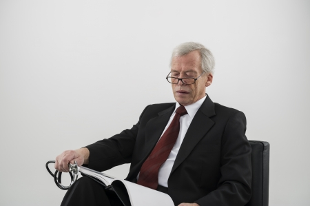 Elderly physician or doctor wearing glasses and holding a stethoscope coiled in his hand seated in a chair reading a medical journal to keep abreast of new treatment and technology, studio portrait