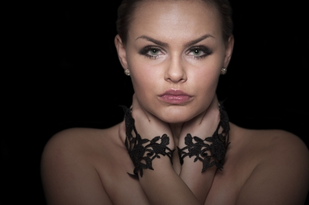 shadowy: Dramatic shadowy cropped head and shoulders portrait of a beautiful woman wearing black lace hand ornamentation holding her throat with her hands and looking at the camera with a serious expression