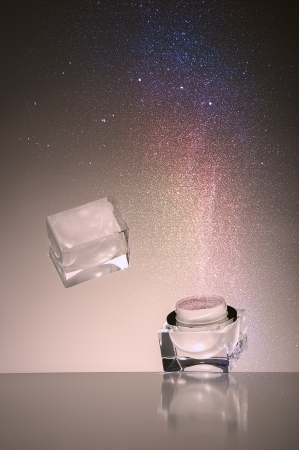 Studio shot of a dropped transparent glass cosmetic jar falling and bouncing off a reflective surface with a fine cloud of colourful cosmetics powder suspended in the air above it