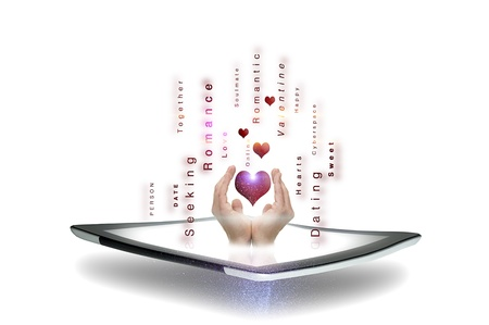 soul searching: Conceptual image of online dating and romance with a mans hands cupping a heart above a tablet screen surrounded by streaming text pertaining to courtship on a white background Stock Photo