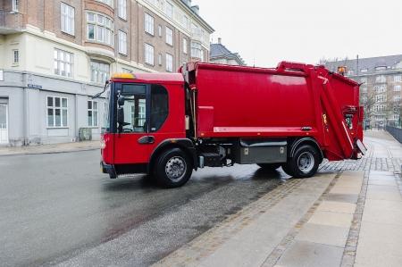 camion de basura: Red cami�n triturador de basura estacionado a un lado de una calle de basura dom�stica recogida de residuos y para la trituraci�n, reciclado y tratamiento o eliminaci�n en vertederos municipales Editorial