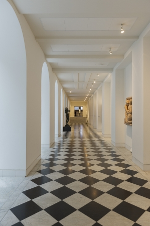 Long interior passage with black and white patterned geometric tiled floor and arches along the length on the left hand side with alcoves on the right Stock Photo - 18832270