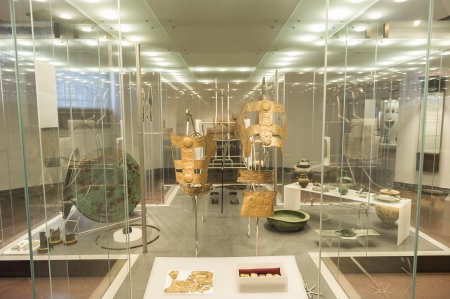 Display of antiquities or art in a museum interior displayed in a large spacious glass display case in a bright airy room with overhead lighting