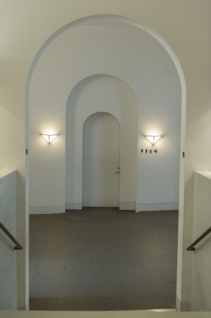 diminishing: Series of three arched doorways in diminishing sizes in neutral colours over a hardwood floor with the central arch flanked by burning wall lamps Editorial