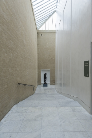 double volume: Passage with descending shallow steps leading down to a bronze statue with double volume walls painted in neutral colours and a glass ceiling