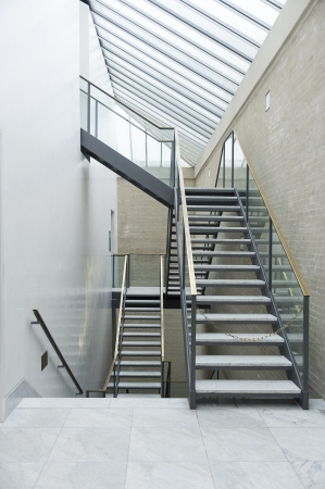 skylights: Modern interior staircase with a steel frame, open treads and a transparent glass bannister on multiple levels under a glass skylight ceiling