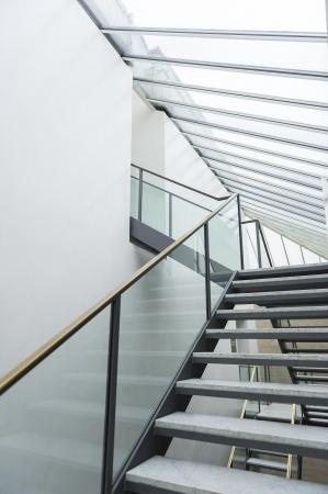 Moderne trap met open treden en een glas Bannister leiden via meerdere niveaus aan de ingang van een zolderkamer in een commercieel gebouw met een glazen dakraam plafond