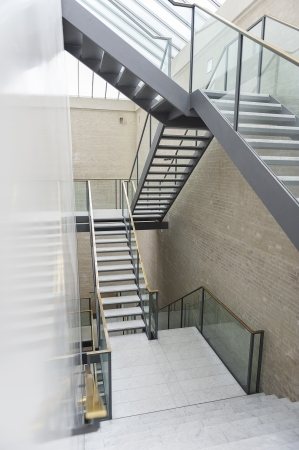Multi level modern staircase in steel with open treads and a glass bannister under a bright airy glass skylight ceiling in a commercial building Stock Photo - 18832277