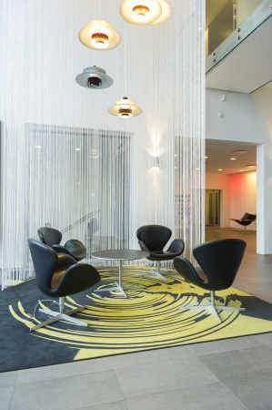 Modern modular table and chairs on a spiral pattern carpet with a spiral light fitting above in the bright airy atrium of a commercial building