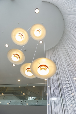 Modern overhead lighting fixture or chandelier consisting of five lights mounted in a hanging spiral at different heights from a high volume ceiling in a commercial building