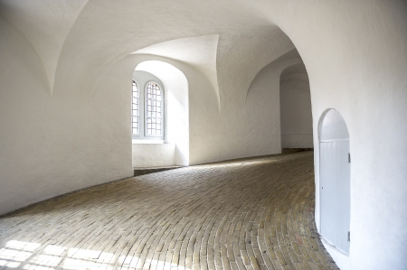 Curved walkway or driveway in a modern building interior with white painted integral arches and ceilings with flowing lines