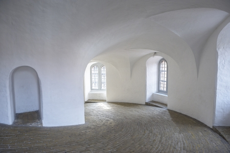 Curved brick walkway or driveway disappearing around a bend in a modern building interior with white painted integral arches and ceilings with flowing lines Stock Photo - 18832120
