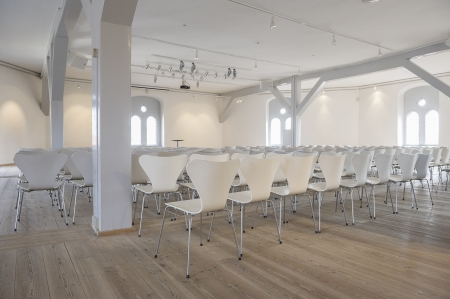 airy: Conference venue or lecture hall with multiple rows of contemporary white seats in a bright airy room with arched windows and wooden beams and supports