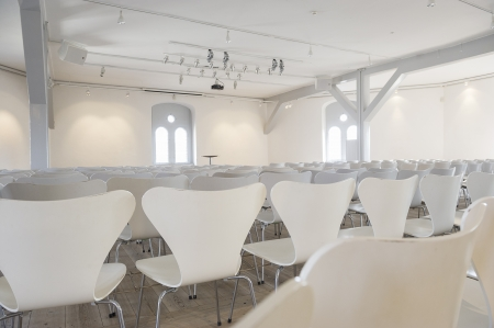 Back view of rows of empty modern white modular seats in a white painted room with lots of daylight from large windows Stock Photo - 18832268