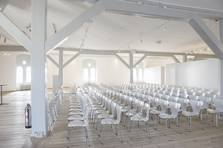 Side view of long rows of modern white seats in a bright airy venue with large windows and white painted wooden structural elements Stock Photo - 18832275