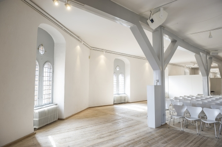 Light airy venue for meetings with large arched windows letting in daylight on a curving wall with rows of modern white chairs arranged in rows on a hardwood floor