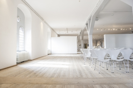 Open spacious auditorium with lots of light and white painted walls and structural elements with white chairs arranged in rows on a hardwood floor Stock Photo - 18832262