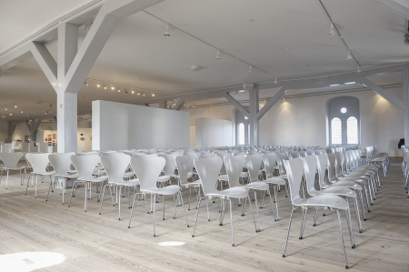 Side view of long rows of modular modern white chairs in a venue with white painted walls and wooden beams and lots of light and space Stock Photo - 18832272