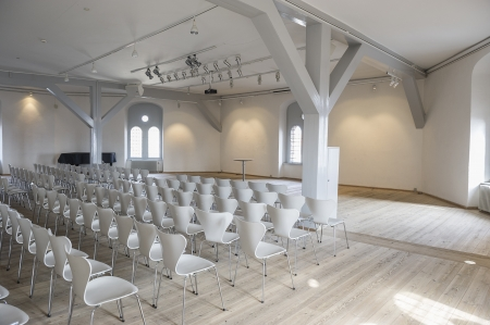 Modern bright airy meeting venue with rows of modular contemporary white chairs, large windows and white painted ceiling, walls and structural elements