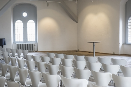 Modern white modular seating arranged in rows in a bright airy lecture hall, view from behind facing a small circular podium or table Stock Photo - 18832264
