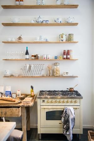 Klein appartement kitchenette interieur met een moderne gaskookplaat en eenvoudige open wand planken met een kleine houten tafel