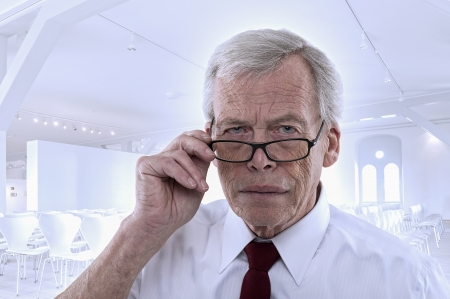 shirtsleeves: Handsome grey haired senior business man lowering his glasses and peering