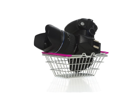 Modern dslr camera, lens and lenshood in a metal shopping basket on a white background conceptual of retail, consumerism and purchasing Stock Photo - 18960128