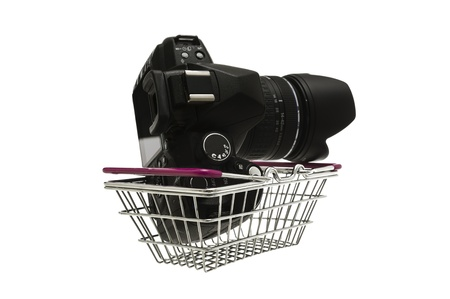 facing to camera: Camera with attached lens and lenshood resting in a small wire shopping basket facing away, conceptual image isolated on white