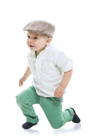 natty: Dapper little boy in a cute outfit with a cloth cap, white shirt and green trousers rising to his feet with a look of delighted anticipation, isolated on white with a small reflection