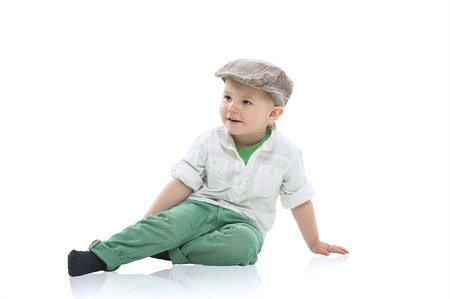 natty: Handsome little boy in a cloth cap and smart green outfit sitting relaxing on a white studio floor with copy space Stock Photo