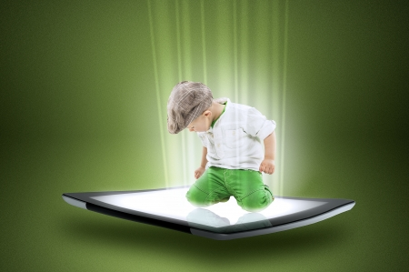beam of light: Conceptual image of a cute dapper little boy in a cap kneeling on the touch screen of a modern tablet computer with data and information streaming around him forming a beam