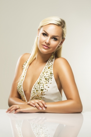 busty woman: An attractive blonde woman sitting down looking at the camera. Stock Photo