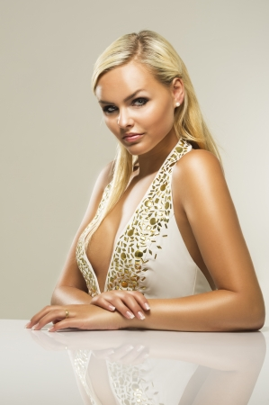 busty: Beautiful glamorous busty blond woman with a lovely tan and serious enigmatic look wearing a stylish low cut dress with a plunging neckline sitting at a table, studio portrait of an exotic sexy woman Stock Photo