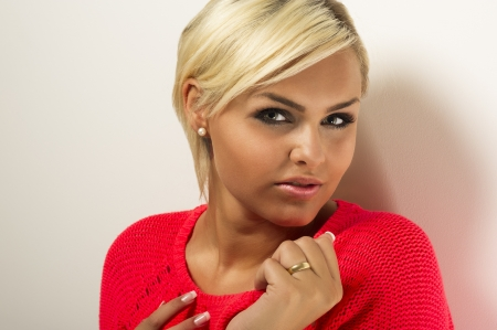 Studio portrait of a glamorous blond woman with beautiful manicured nails and tanned skin looking at the camera with her head turned to the side