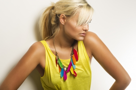 Portrait of a beautiful tanned blond woman with her hair in a ponytail covering her eyes wearing a colourful ethnic necklace with feathers