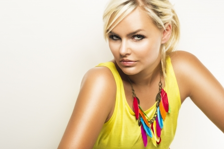 sultry: Beautiful blond woman giving the camera a sultry seductive look wearing a colourful trendy necklace, head and shoulders studio portrait Stock Photo