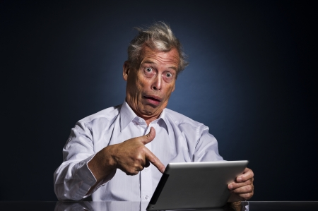 Shocked senior man pointing to his tablet computer with his finger with a look of appalled disbelief and confusion, humorous upper body studio portrait photo