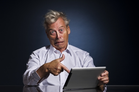 overwrought: Emotional senior business man with an expressive face pointing to his laptop in horror and disbelief as he sits at a table against a dark studio background with copyspace