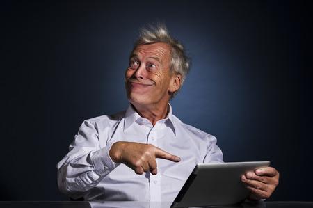 Senior zakenman grijnzend met een blik van dwaze zelfgenoegzaamheid en wijst naar zijn tablet-computer