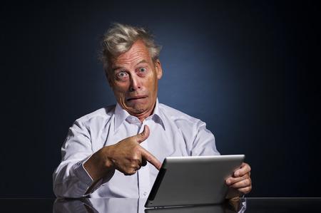 Emotionele senior business man met een expressief gezicht te wijzen op zijn laptop in afschuw en ongeloof