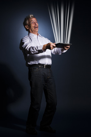 Conceptual image of a senior business man holding a tablet-pc radiating beams of glowing light